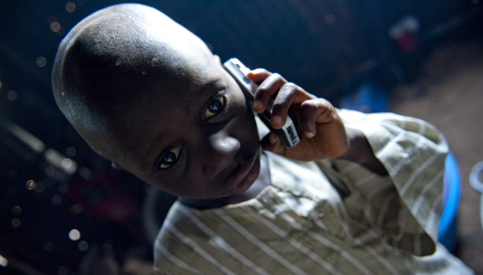 Young child listens on a mobile telephone