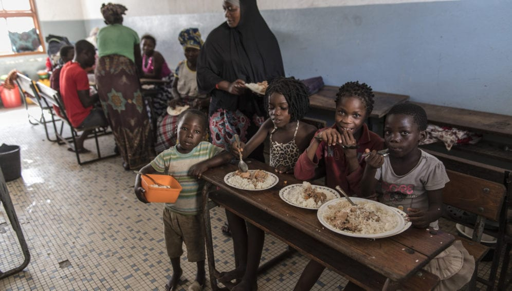 Children eating hot meals provided by a community kitchen