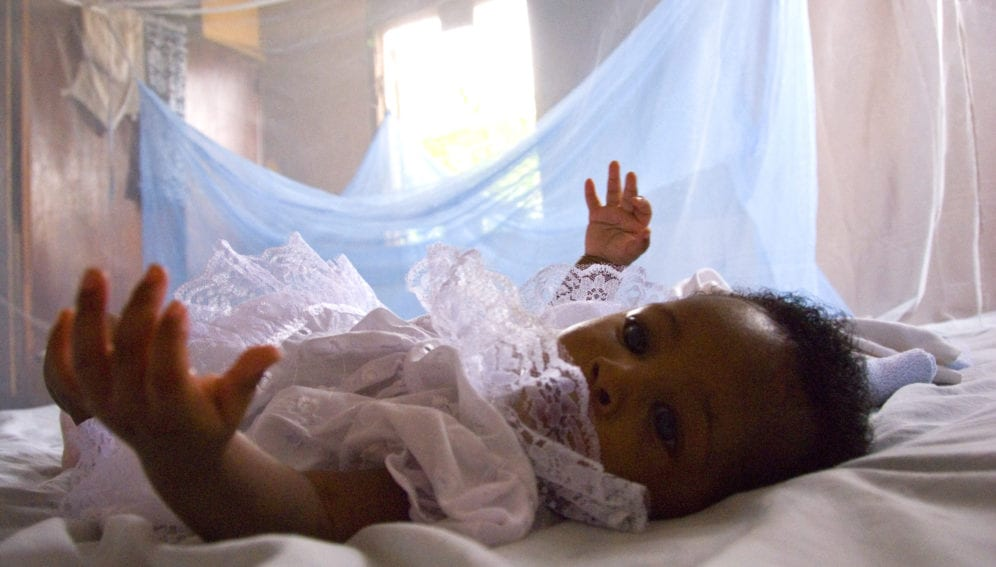 Infant surrounded by protective malaria bed net