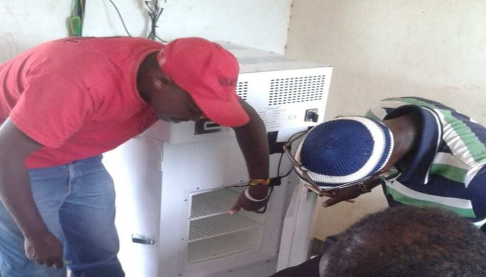 A technician training dispensary worker on use of solar refrigerator in North Eastern Kenya