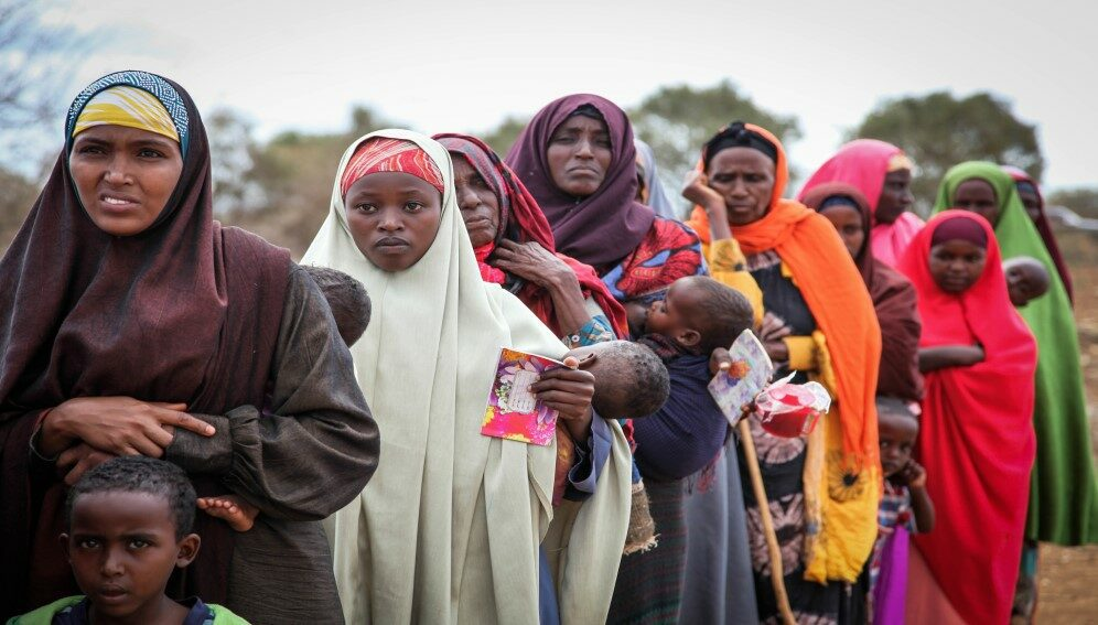 Women and children queue to enter a free medical clinic